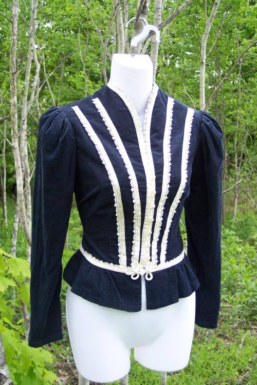 on a dress maker's dummy, a blue velvet mutton sleeve top with lines of white lace.